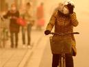行人冒着风沙在巴彦淖尔临河区街头骑行